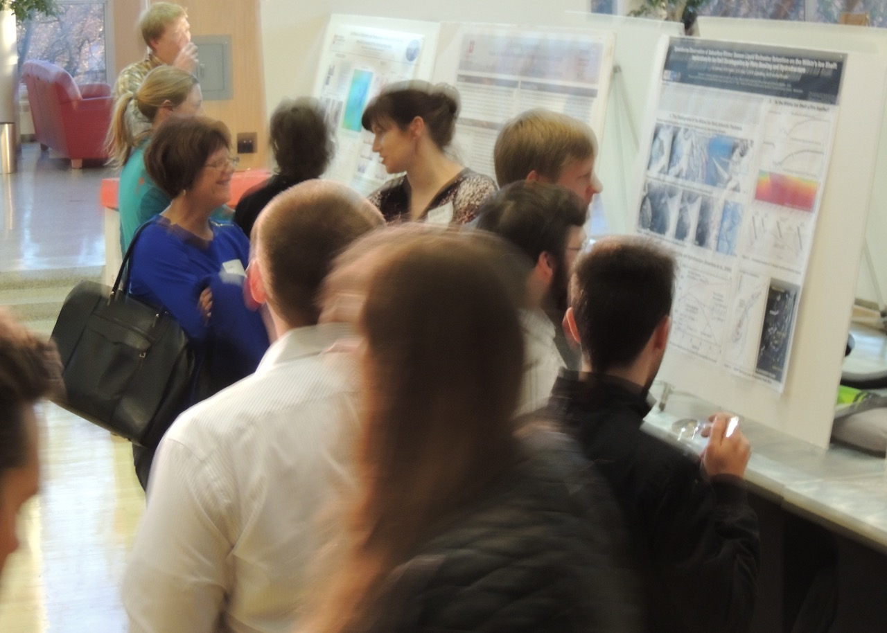 people talking and viewing research posters