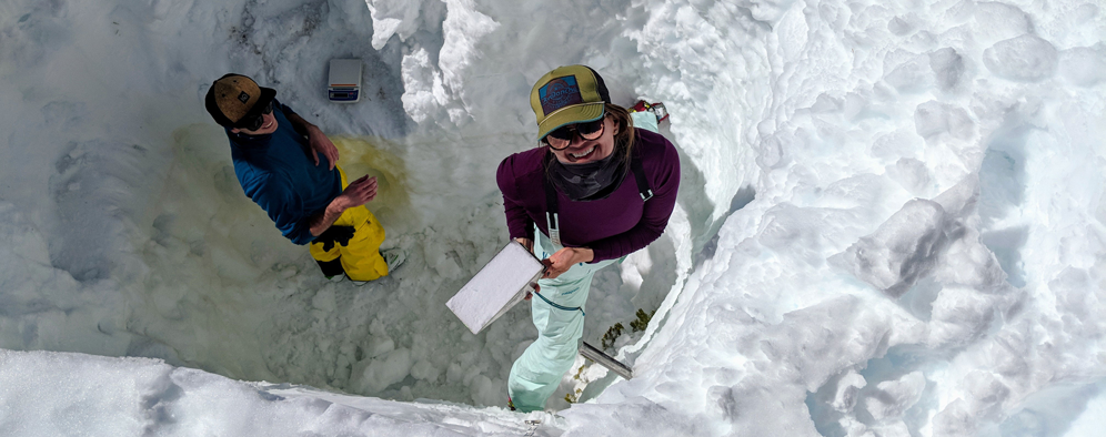 2 researchers with equipment in deep snow pit