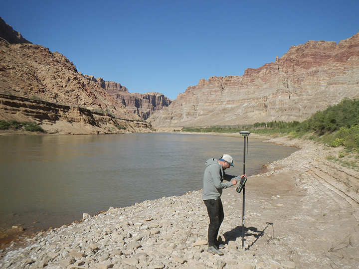 researcher with instrument on canyon river bank