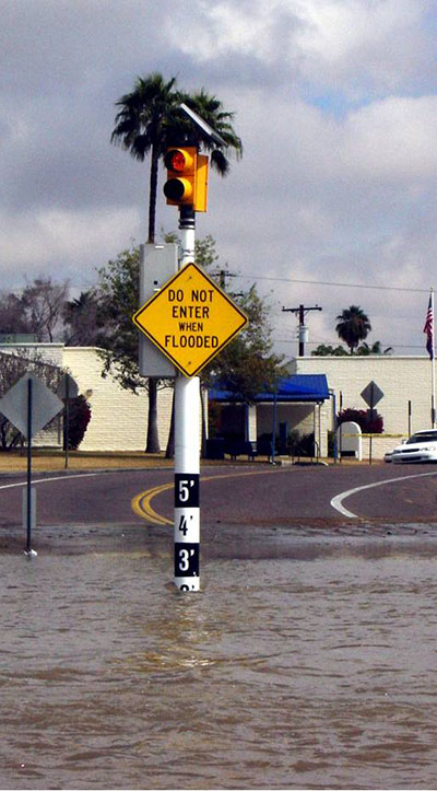Signpost standing in floodwater nearing 3 foot mark says do not enter when flooded.