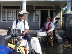 Rescuer on a water craft in front of a flooded home where a man wearing waders is carrying items out of the house.
