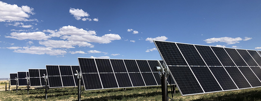 An array of solar panels against a blue sky dotted with white clouds.