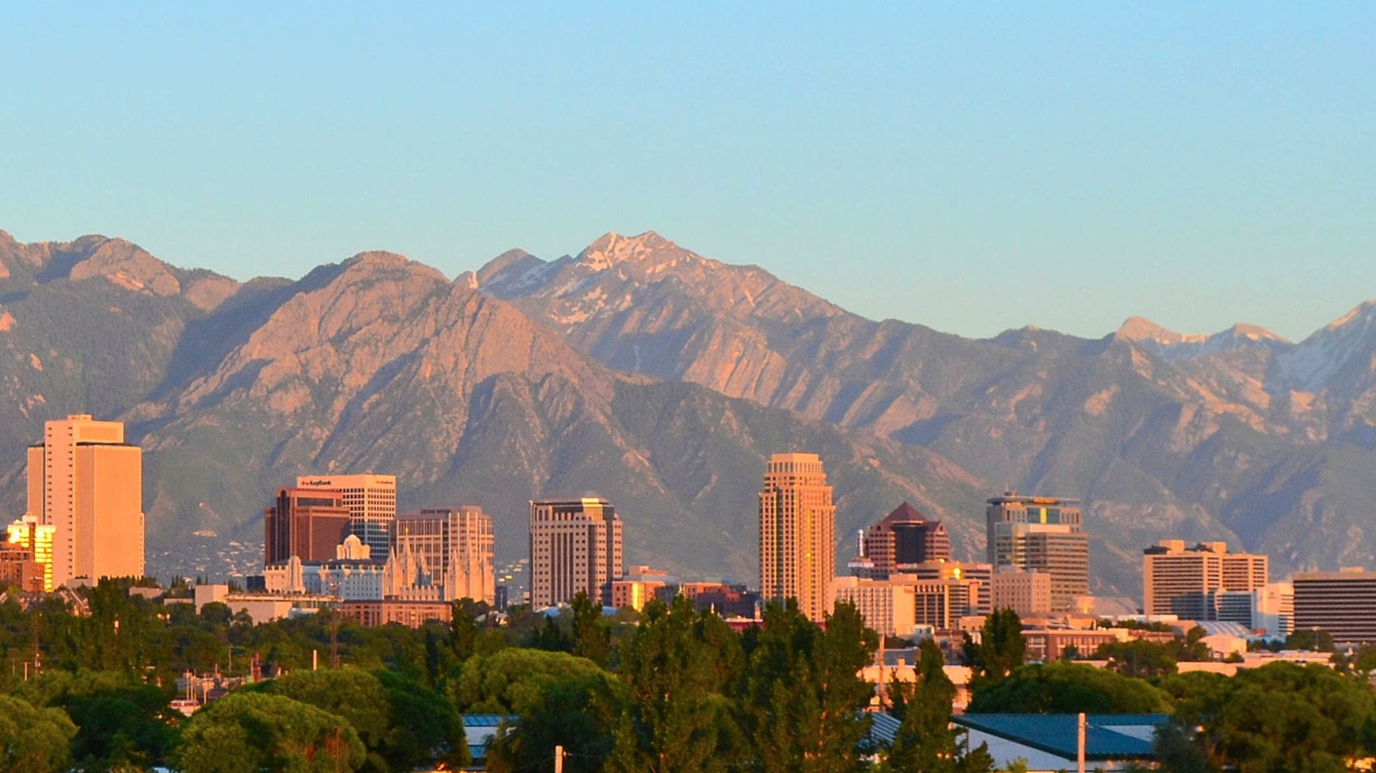 Tall buildings in Salt Lake City against the Wasatch Mountains, under a blue sky