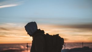 profile of a person wearing a hoodie and a large backpack against an orange sunset