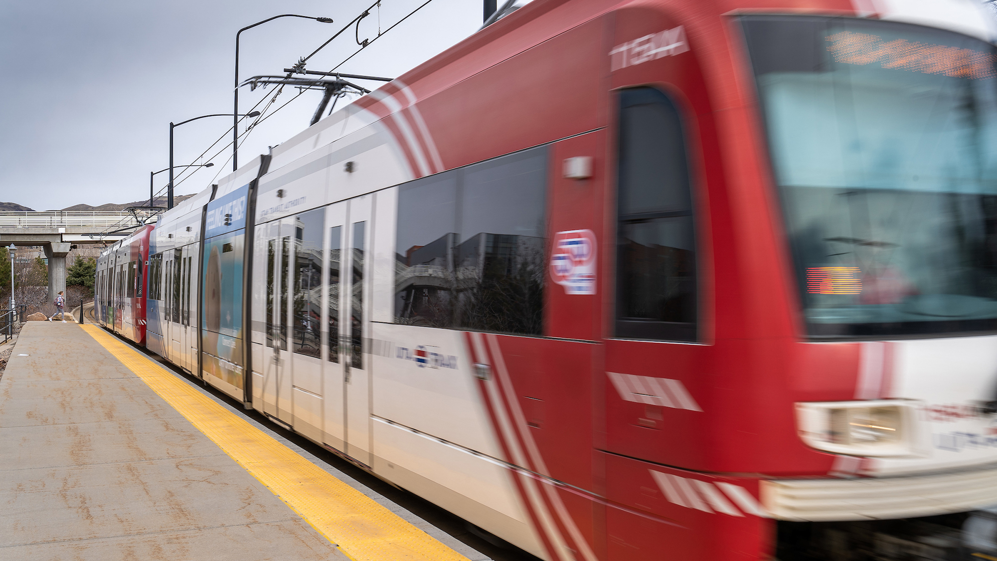 A red and white TRAX light rail train blurred by motion