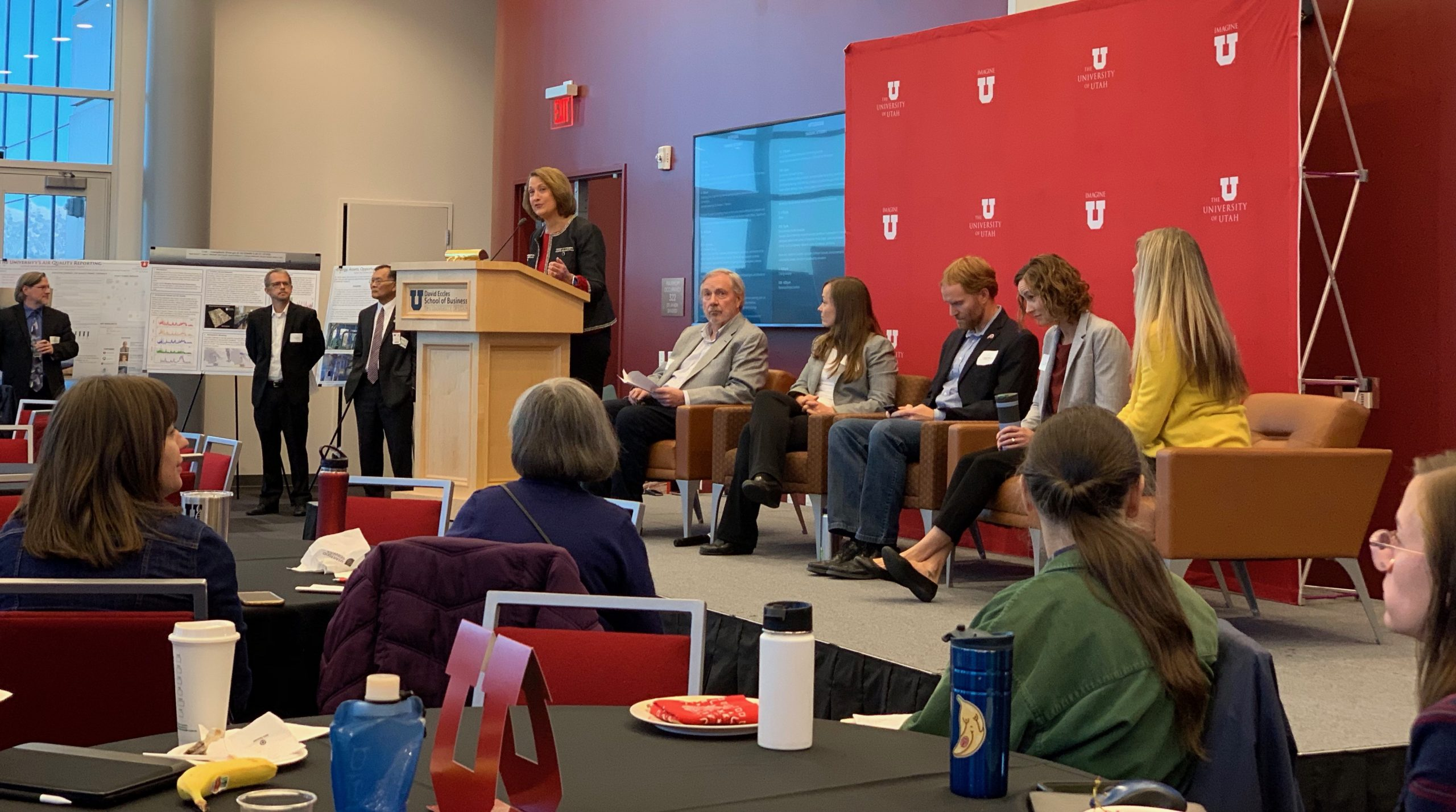 President Ruth Watkins stands at a podium next to five seated panelists. Attendees are seated and standing around the room.