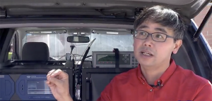 John Lin sits in front of air monitors mounted in a vehicle
