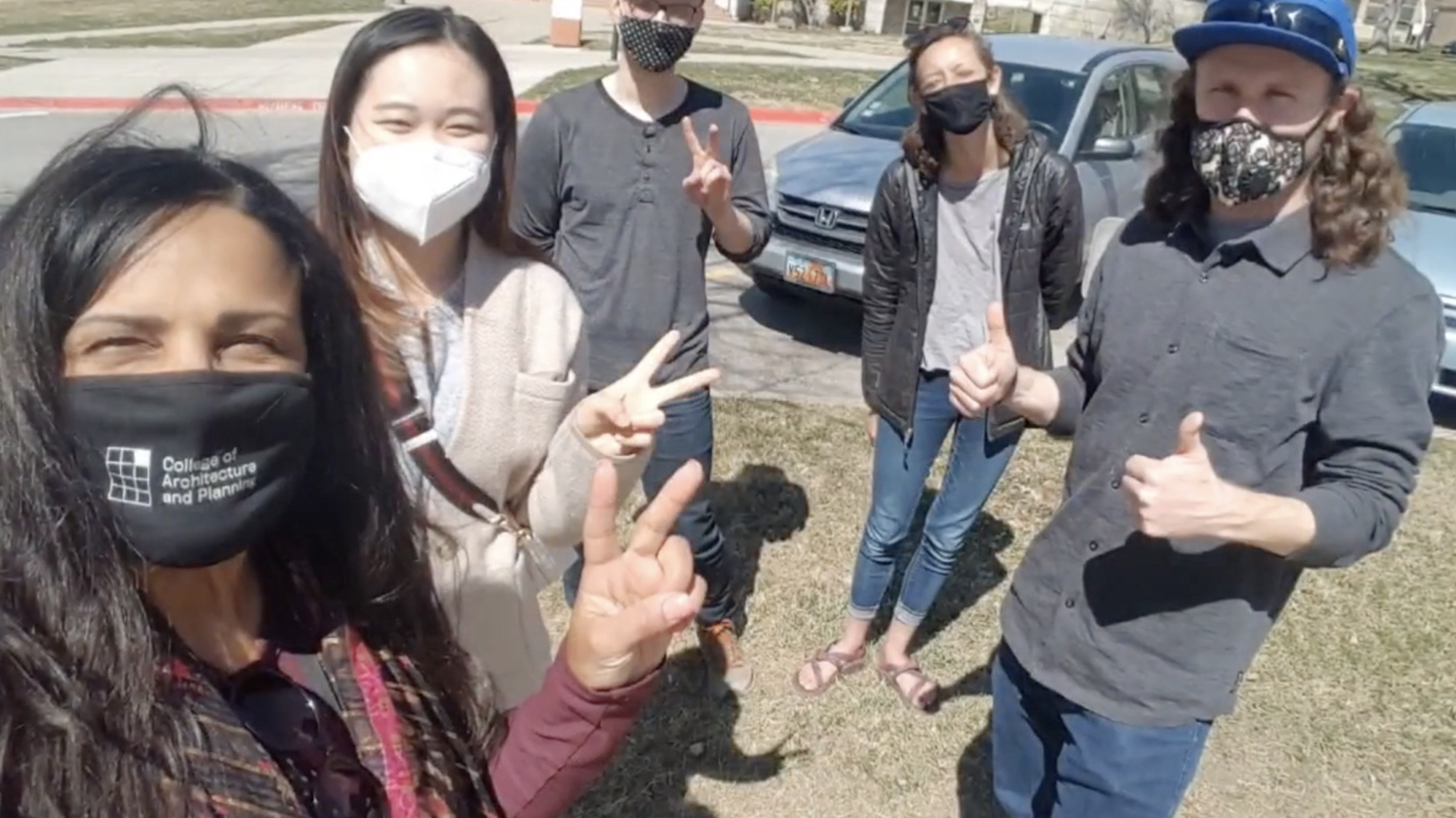 Five university students are wearing masks and giving approval hand signs (thumbs up, Vee). They are standing on grass. Two cars and a building are visible behind them.