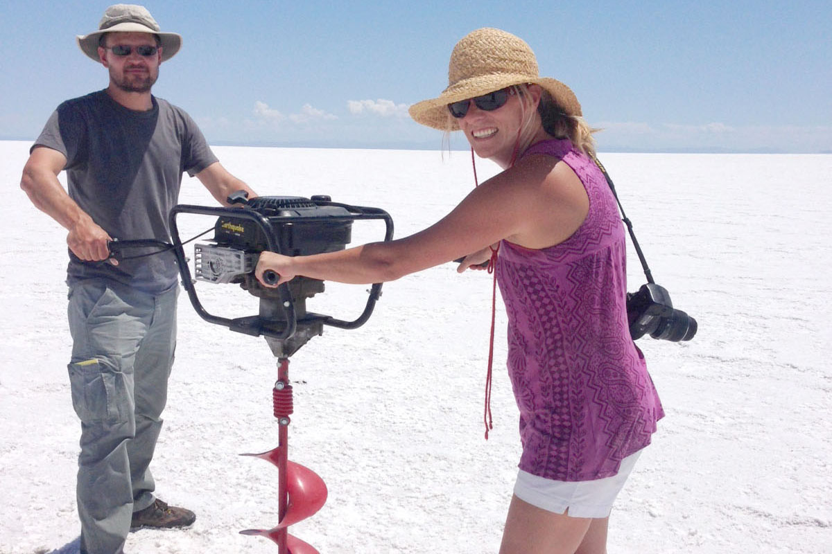 A man and a woman are standing on a white expanse of salt under a blue sky. They are gripping the four handles of a chest-high industrial drill.