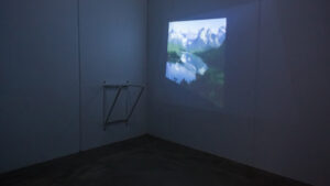 A darkened room, empty except for a metal fixture attached to the wall. There is a projection on the adjoining wall of a color photo of snow-capped mountains with evergreens nestling a blue lake.